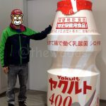 With a giant Yakult bottle.